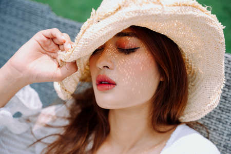 Close up portrait - Beautiful asian woman traveler wear hat outdoors.