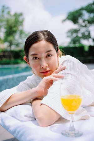 Portrait of asian woman in white bathrobe at spa treament bed near swimming pool.
