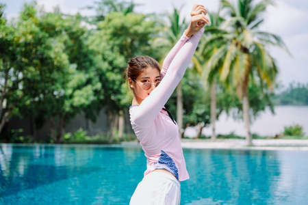 Beautiful asian woman traveler stretching arms up in the air at swimming pool. 版權商用圖片