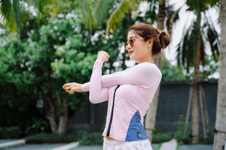 Beautiful asian woman traveler stretching arms before exercise outdoors.