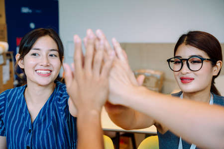 Business team giving a high fives gesture as they laugh and cheer for their success.