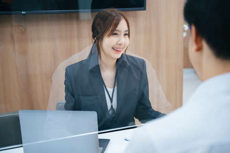 Beautiful asian receptionist giving information to customer behind the desk. Banque d'images