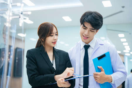Young asian doctor and beautiful secertary working together in hospital or clinic.