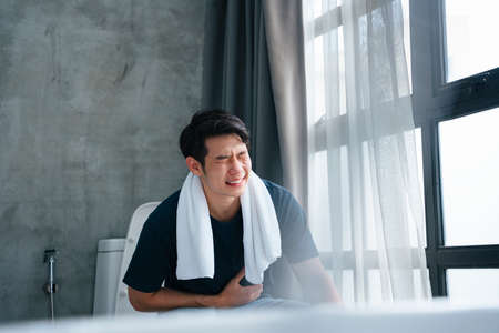 Asian young man in the toilet with problems of constipation. Stockfoto