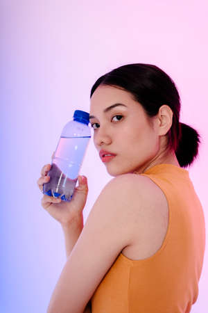 Portrait of young sport healthy asian woman with bottle of water isolate on pastel background.