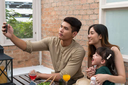Asian family taking selfie with smartphone while having lunch at restaurant.