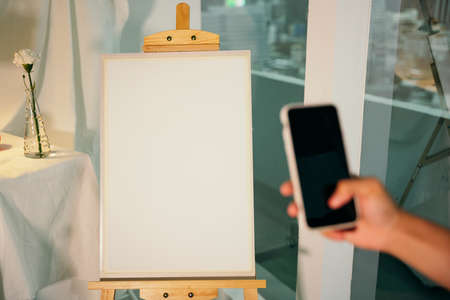 Artist taking picture of empty canvas with smartphone. Mock up design.