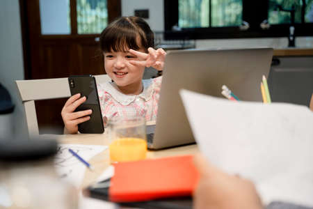 Cute little girl selfie or vlogging with smartphone infront of laptop computer.