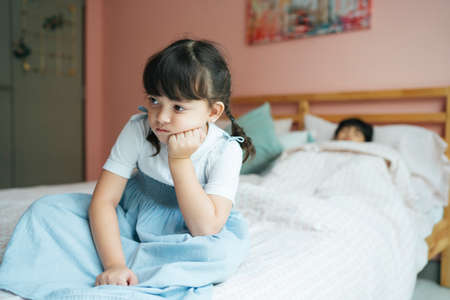 Little girl tire of taking care of her sick brother in bedroom.