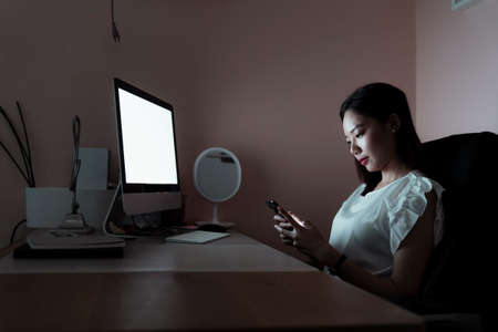 Asian woman working infront of the computer at night, using smartphone for working. Copy space.