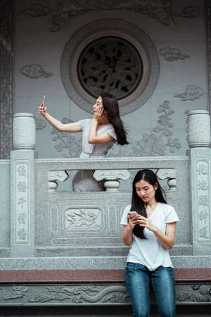 Two asians women using smartphone on the different floors in Chinese temple.