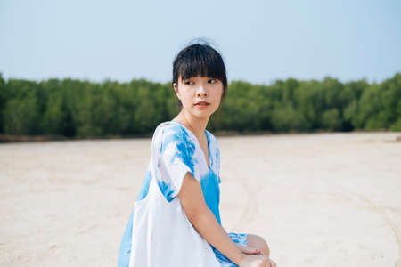Black hair French braid girl in white and blue tie dye sit on the sand land with her white canvas bag, horizontal.