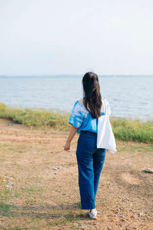 Back shot of black half tied hair girl in white and blue tie dye walking in grassland next to the sea with canvas bag in sunlight.