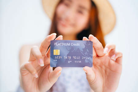 Portrait of asian pretty young woman wearing hat and white dress holding credit card with both hands.