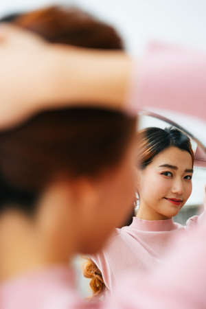Portrait of beautiful asian woman tying hair looking at mirror.