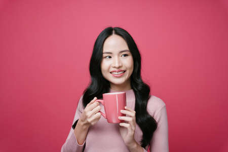 Portrait of young asian woman holding coffee cup isolate on pink background.