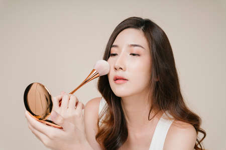 Portrait of beautiful young asian woman applying cosmetic powder on her face. Imagens