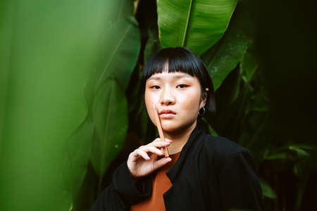 Portrait of young asian woman short hair holding pen like cigarette in nature.