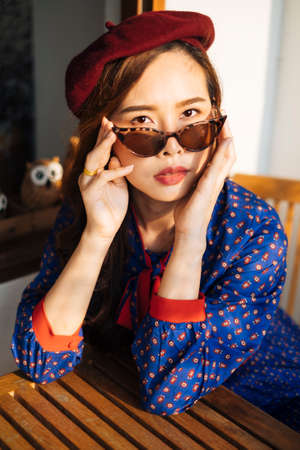 Wavy brunette woman in blue and red retro dress and sunglasses sitting at the wooden table next to glass window with owl.