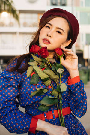 Close up shot of wavy brunette woman in blue and red retro dress hold the rose and look at the sea. Imagens