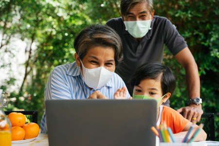 Asian grandparents and grandson wear mask doing video call with someone on laptop at yard.
