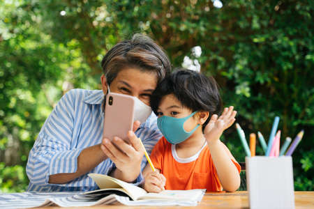 Senior elderly old woman wear mask using smartphone together with her grandson.