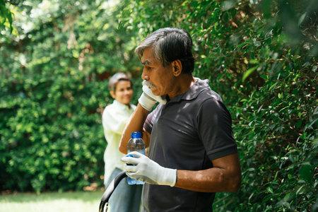 Senior elderly old man take a break drinking water after working at garden.