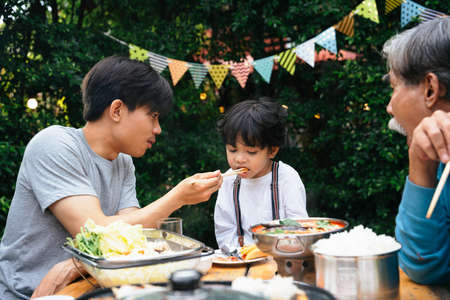 Asian father feeding food to son in dinning party outdoor. Banco de Imagens