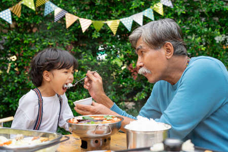 Grandfather feeding food to grandson in birthday party outdoor.