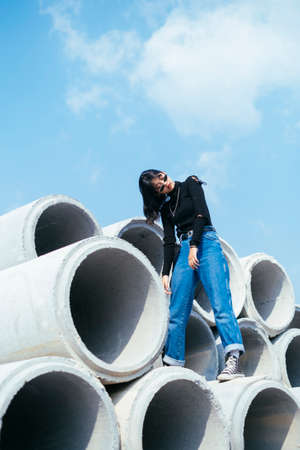 Tired fashionista girl in black sweater and jeans standing on big concrete tube in sunlight like a zombie. Imagens