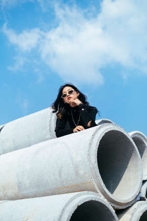 Fashionista girl in black sweater and jeans standing and bend down on big concrete tube.