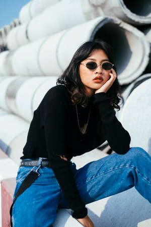 Fashionista girl in black sweater and jeans sitting on red and white barricade and prop her foot on the big concrete tube.