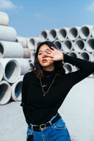 Fashionista girl in black sweater and jeans standing in quiet place full of big concrete tube raise her hand cover her face. Imagens