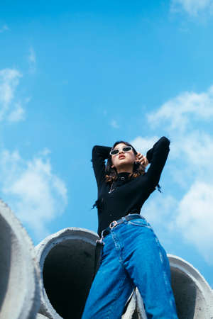 Fashionista girl in black sweater and jeans standing on big concrete tube in sunlight raise her hands at the back.