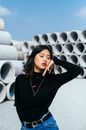 Fashionista girl in black sweater and jeans standing in big concrete tube area touch her face. Imagens