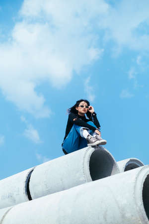 Black hair girl in sweater and jeans sitting on the top of big concrete tube with knees up and grab her sunglasses. Imagens