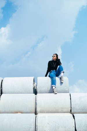 Black hair girl in sweater and jeans chilling sitting on the top of big concrete tube.