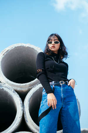Low angle shot of fashionista girl in black sweater and jeans swearing sunglasses tanding on the big concrete tube and pick her pocket under blue sky.