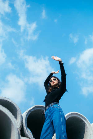 Fashionista girl in black sweater and jeans standing on big concrete tube raise her hands up.