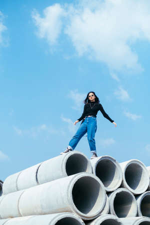 Fashionista girl in black sweater and jeans dangerous standing on big concrete tube under cloudy blue sky.
