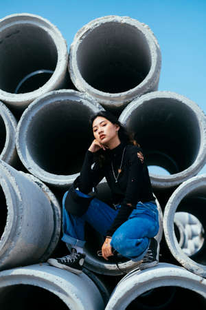 Cool posture sitting of fashionista girl in black sweater and jeans on big concrete tube under blue sky.