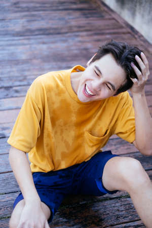Guy in yellow t-shirt and blue pants sitting on the wooden floor after fall down into the lake and get wet, he laugh at himself.