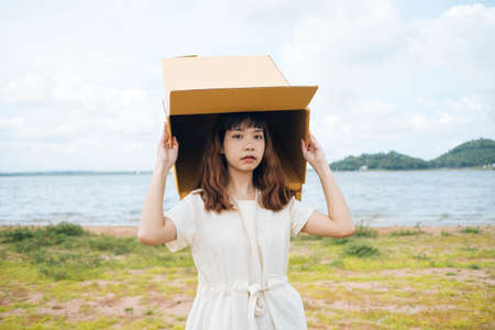 Young asian thai woman hipster curly hairstyle on white dress playing with cardboard box putting over head at lake.