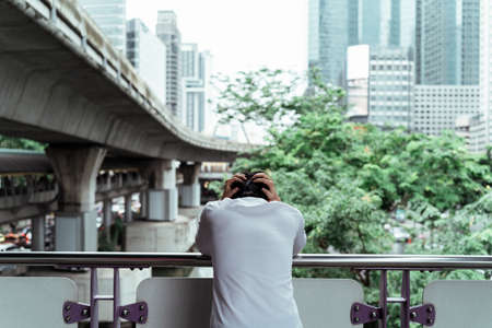 Sad adult business man leaning on the handrail on overpass. Stressful business man standing on the city bridge covering his head with hands. Stock Photo