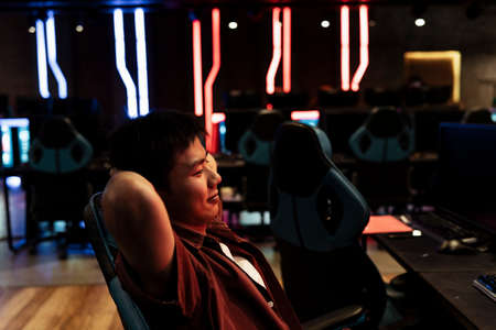 Happy asian gamer relax on gaming chair after winning the lasted game.