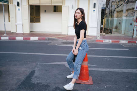 Full length fashion portrait - Beautiful hipster asian young woman in black shirt and jeans pants sitting on red traffic cone on the road.