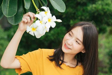 Black long hair girl enjoy playing the white plumeria flower and smile.