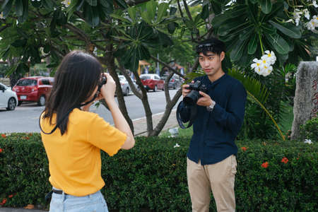 Male photographer take a photo of teenage model girl at the plumeria tree while she hold the flower and camera.