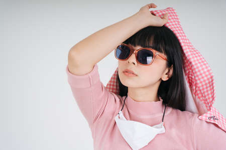 Fashion portrait - Beautiful asian thai long dark hair woman in pink jacket wearing sunglasses over white background. Stock Photo