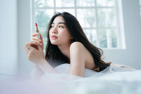 Wavy long hair woman lie down on stomach on the bed in the morning and holding the lipstick then rotates it.